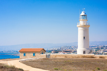 Old white lighthouse near the ancient ruins in Paphos Archaeological Park, Cyprus