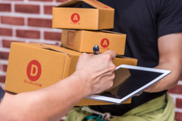 receiver sign on tablet when receive a package box from delivery man