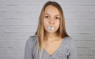 Portrait of teenage girl blowing balloon from chewing gum