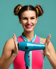 Happy young brunette woman hold green hair dryer smiling on blue mint background