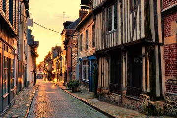 Fototapete - Old street in the Normandy town of Honfleur, France with light of the rising sun