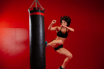 Young woman exercising bag boxing in studio. Portrait of a girl with black boxing gloves on a red background. Sport woman jumping. Athletic brunette wearing boxing gloves. Fight Sport concept.