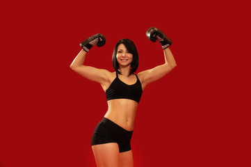Woman celebrating victory with arms up wearing boxing gloves on red background.