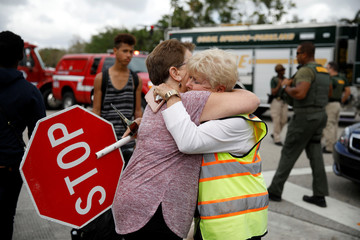 People embrace during student protest following mass shooting in Parkland