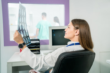 Female doctor looking at an x-ray in her office