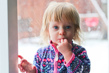Close-up Portrait of Cute Blonde 18 Month Old Toddler Girl with Big Blue Eyes, looks at camera, sucking fingers, Sweet Face Expression, Stand by the Window, Snowy Background