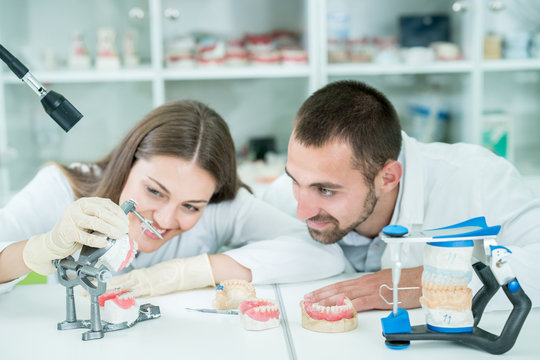 Young team of dental technicians making teeth prostetics. Process of making denture.