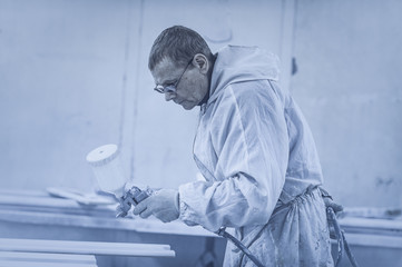 Man painting furniture details. Worker using spray gun. Toned image.