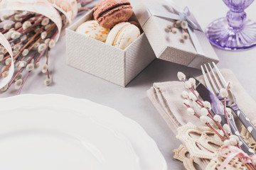 White plate, purple glass, cutlery, present box with macaroons and pussy willow twigs