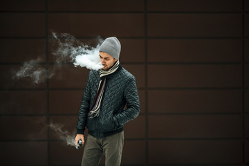 Vape man. Portrait of a handsome young white guy in casual clothes vaping an electronic cigarette and letting out puffs of steam opposite the futuristic modern building. Lifestyle. Close up.
