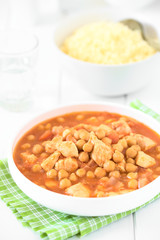 Chicken and chickpea stew or tagine in white bowl with couscous in the back, photographed with natural light (Selective Focus, Focus in the middle of the stew)