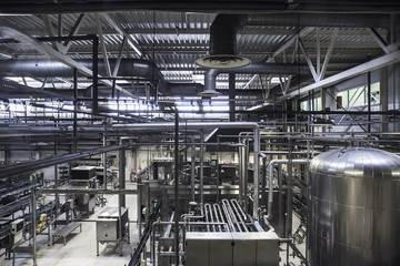 Modern brewery plant. Huge tanks or vat for beer  fermentation, industrial background with many steel pipes