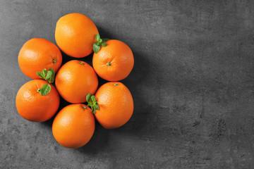 Juicy ripe oranges on dark background, top view
