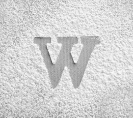 Silhouette of letter W on scattered flour
