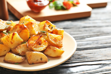 Plate with tasty potato wedges on wooden table