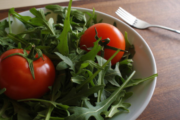 salad of rucola tomato on a wooden background