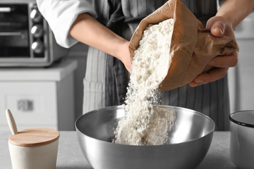 Woman pouring flour into bowl on table