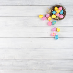 Colorful Easter Egg Nest Overflowing from Up Above with Extra White or Gran Wood Board Background for room or space for copy, text, words. A flat lay with square crop