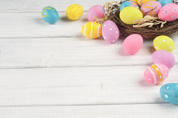 Easter Eggs in Nest in a corner from Top View Looking Down on White or Gray Rustic Shiplap Wood Boards Background with room or space for copy, text or words.  It's a flat lay, shabby chic design