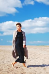 Fashion shoot the sandy beach. Beautiful slender self-confident model posing in elegant coat a bright Sunny day on background of blue sky with floating clouds