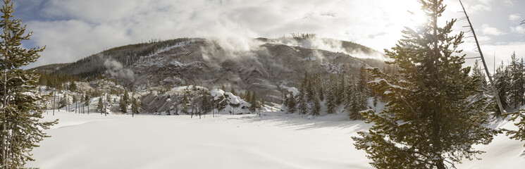Snow covered landscape of Roaring Mountain geyser vents in Yellowstone National Park in winter