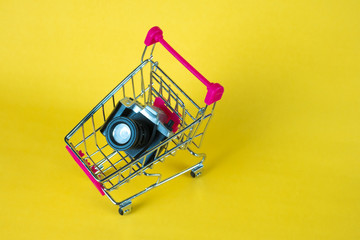 Mini camera toy and shopping cart or supermarket trolley on yellow background, copy space for add text.