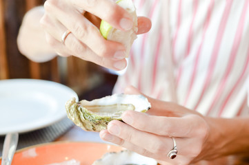 Close up on hand of a woman holding oyster, ice and lemon on platter wooden table background. Closeup of luxury healthy freshness, dieting gastronomy food. Holiday travel vacation lifestyle