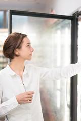 冷蔵庫から飲み物を選ぶ女性