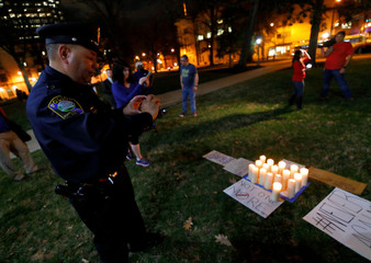 A policeman take pictures of seventeen candles placed in memory of the victims of the shooting at Marjory Stoneman Douglas High School, outside the North Carolina State Capitol building after a demonstration calling for safer gun laws, in Raleigh