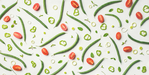 Food pattern, texture and background. Flat-lay of fresh green beans and cherry tomatoes over white wooden table, top view. Healthy cooking, clean eating, vegan, vegetarian, dieting concept