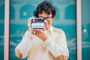young man taking an instant photo