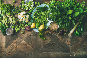Spring healthy vegan food cooking ingredients. Flat-lay of vegetables, fruit, seeds, sprouts, flowers, greens over rustic wooden background, top view, copy space. Clean eating food concept