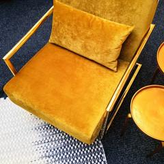 Retro style dark yellow velvet armchair and golden side table