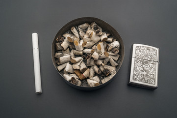 Ashtray cigarette lighter on the background of a gray table