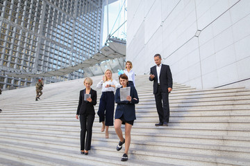 Employees of large  corporation walking in   and speaking by smartphone. Concept of successful business partners outside. Young prosperous people dressed in black suits look happy.