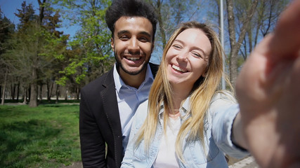 Beautiful couple smiling. Girl has long fair hair, dressed in white T-shirt and jeans jacket. Boy has black hair, beard and dimples on face. Concept of modern technologies for free calls Internet apps