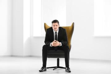 Handsome businessman sitting in comfortable armchair indoors
