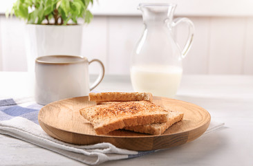 Wooden plate with tasty toasted bread and cup of coffee on table