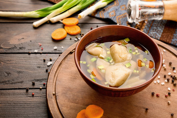 Tasty broth with dumplings on wooden table