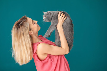 Young woman with cute pet cat on color background