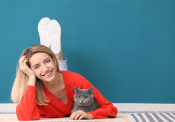 Young woman with cute pet cat on floor