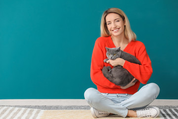 Young woman with cute pet cat against color wall