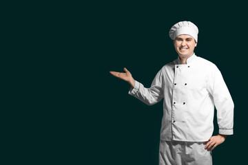 Male chef in uniform on dark background