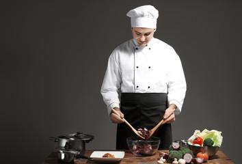 Male chef in uniform cooking against dark background
