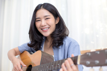 Attractive asian woman playing guitar with smiling at home.