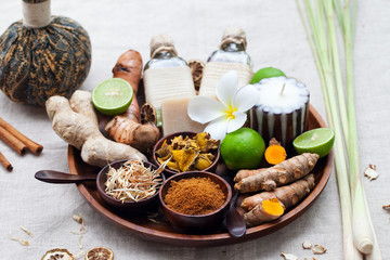 Spa, heath care set of essential oils, soap, ginger, turmeric roots and spices on a wooden tray.