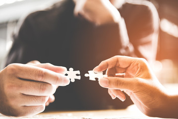 .Businessman team work holding two jigsaw connecting couple puzzle piece for matching to goals target, success and start up new project in office.  Business Concept.