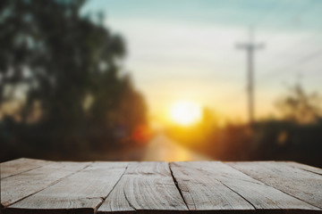 Wood table top in front of of trees in the forest. blur background image, for product display montage in morning light