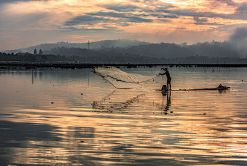 Fisherman in water dam