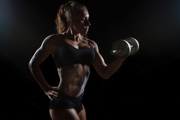 Muscular fitness woman posing with the dumbbell